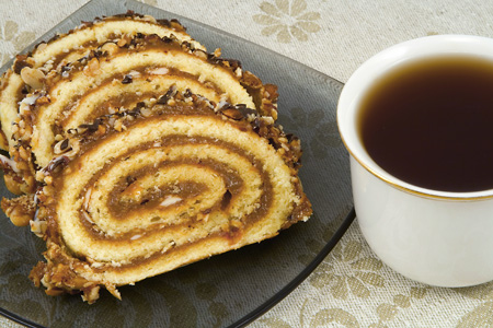 Swiss roll on a plate and cup of tea